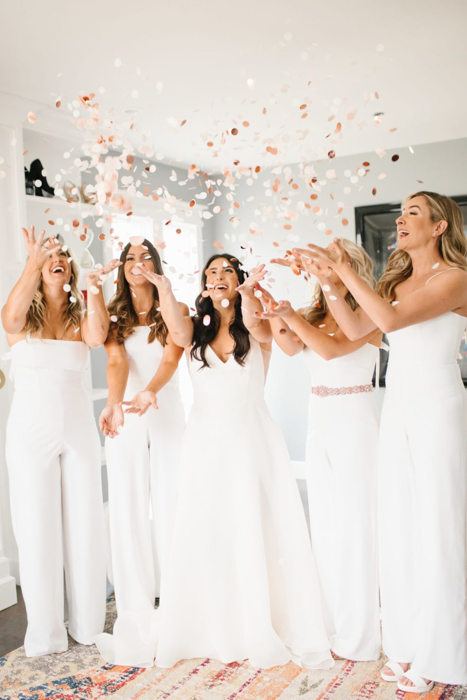 bridesmaids in white jumpsuits toss confetti photographed by Ashley Mac Photographs