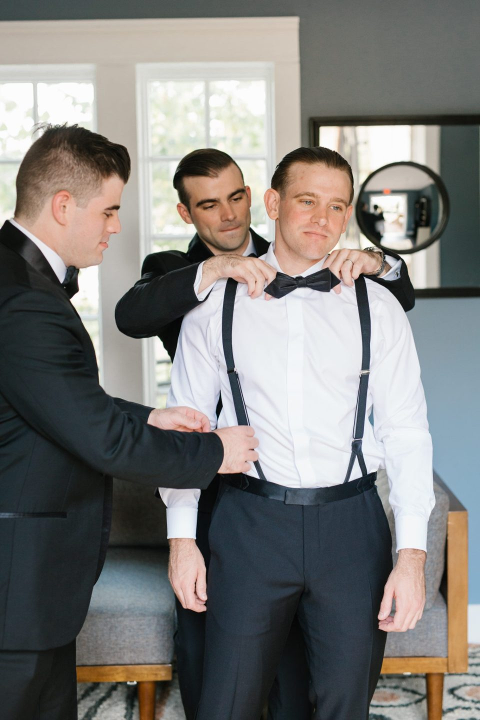 groom gets into suit with groomsmen's help