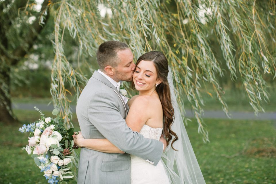 Ashley Mac Photographs photographs happy couple on their wedding day next to willow tree