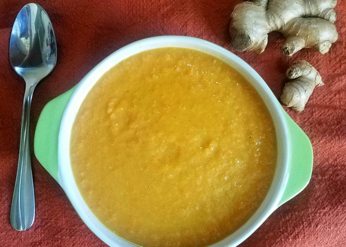 bowl of soup with a spoon and a piece of ginger on the tablecloth