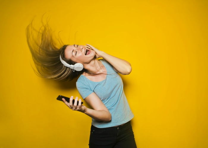 girl flipping hair and dancing to music on her headphones