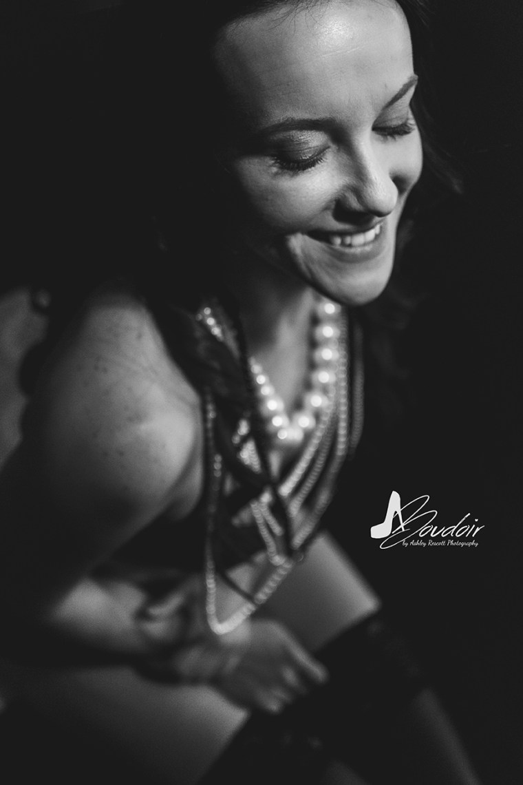 black and white image of sitting woman with pearl necklaces