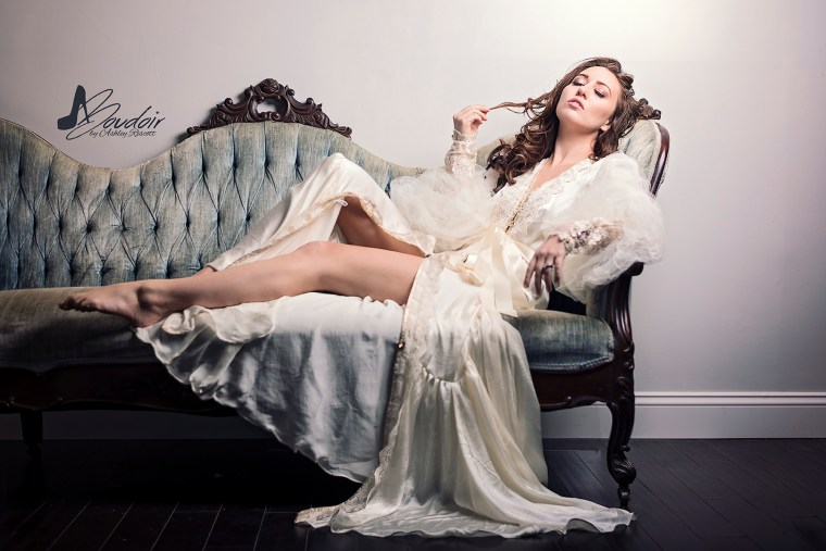 woman in floor length robe reclining on victorian couch