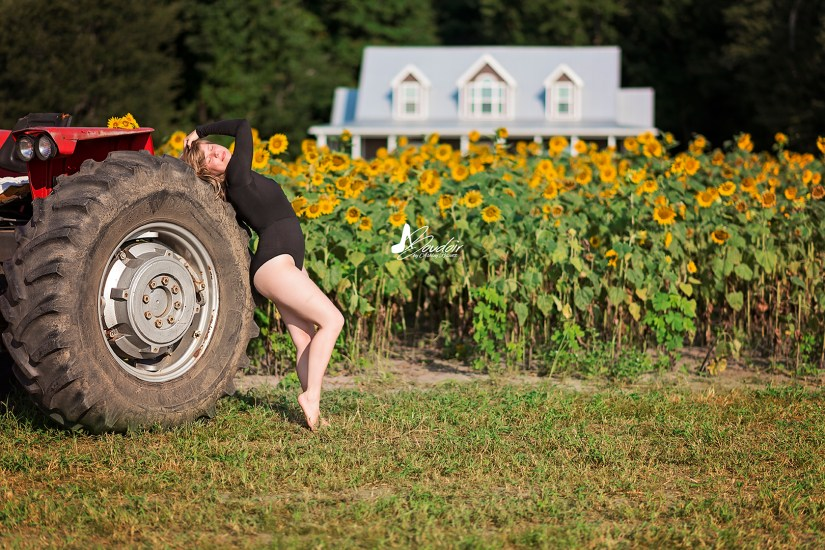 woman leaning on tractor in front of sunflowers
