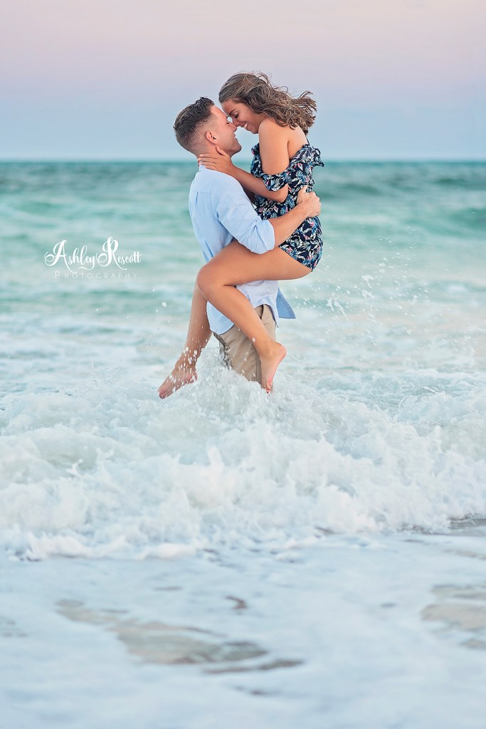couple standing in waves at beach at sunset