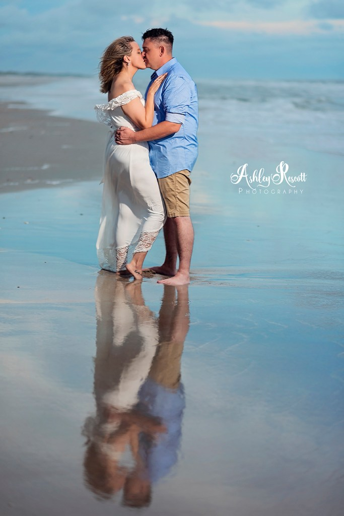Couple reflected in water on beach