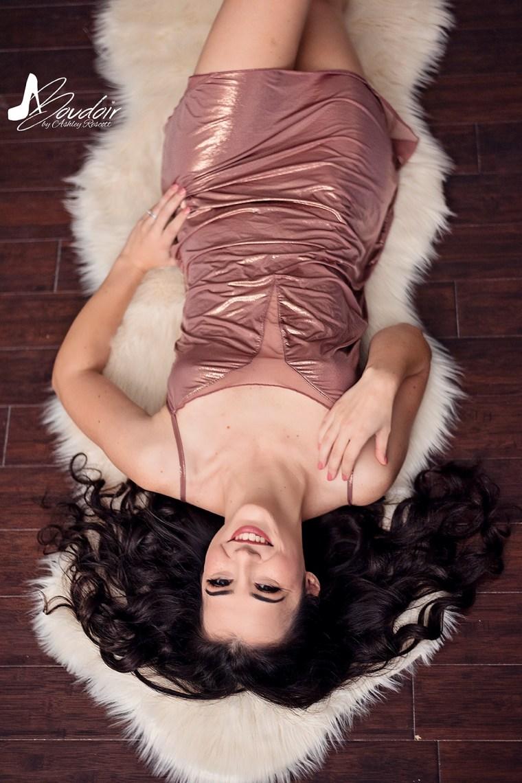boudoir image of woman lying on sheepskin rug