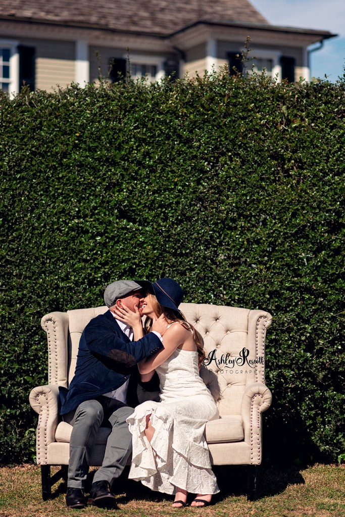 Couple kissing on couch in front of hedge