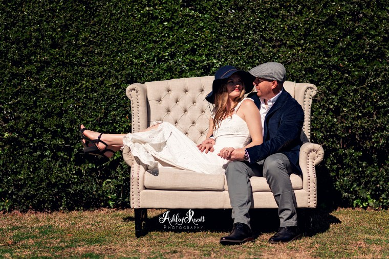 couple sitting on couch, looking at each other, in front of hedge