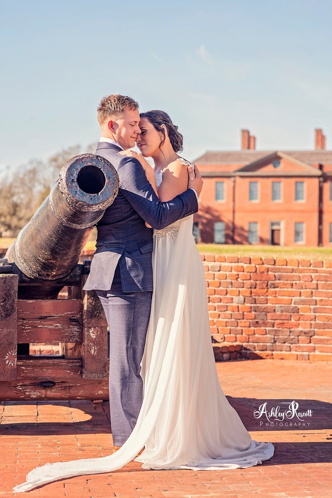 bride & groom leaning against cannon with tryon palace in the background