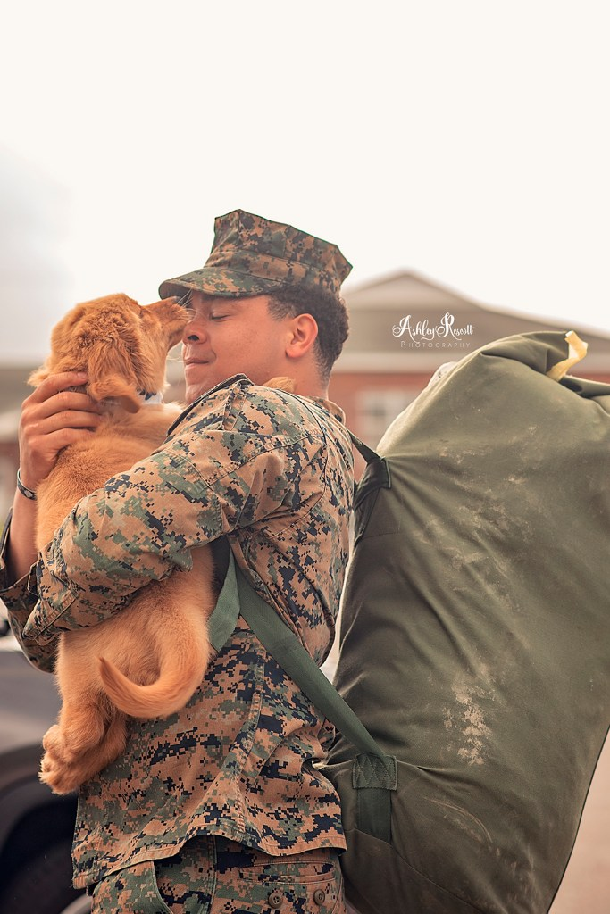 puppy kissing Marine at homecoming