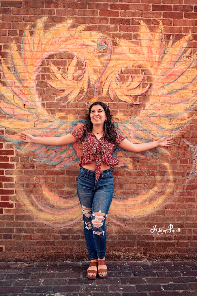 teen girl standing in front of chalk drawn wings on brick wall