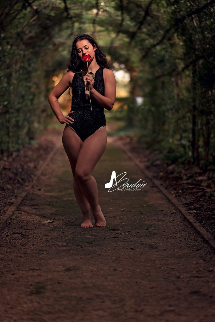 woman smelling rose in allee
