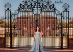 teen girl in prom dress in front of palace gate