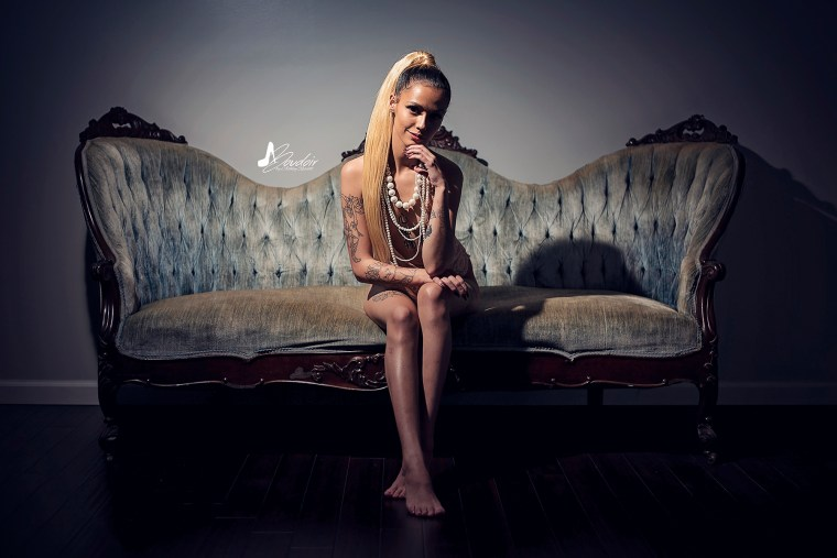 Blonde boudoir model in pink lacy teddy sitting on couch leaning forward with dramatic light