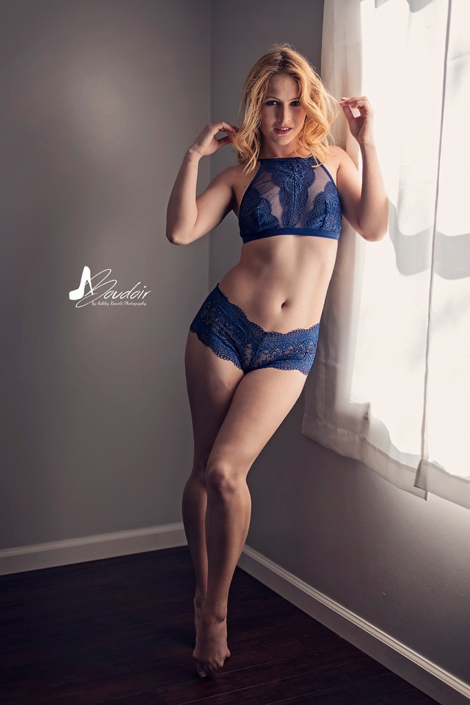woman in blue underwear standing by window