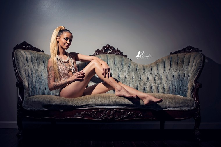 blonde boudoir model sitting on couch in dramatic light