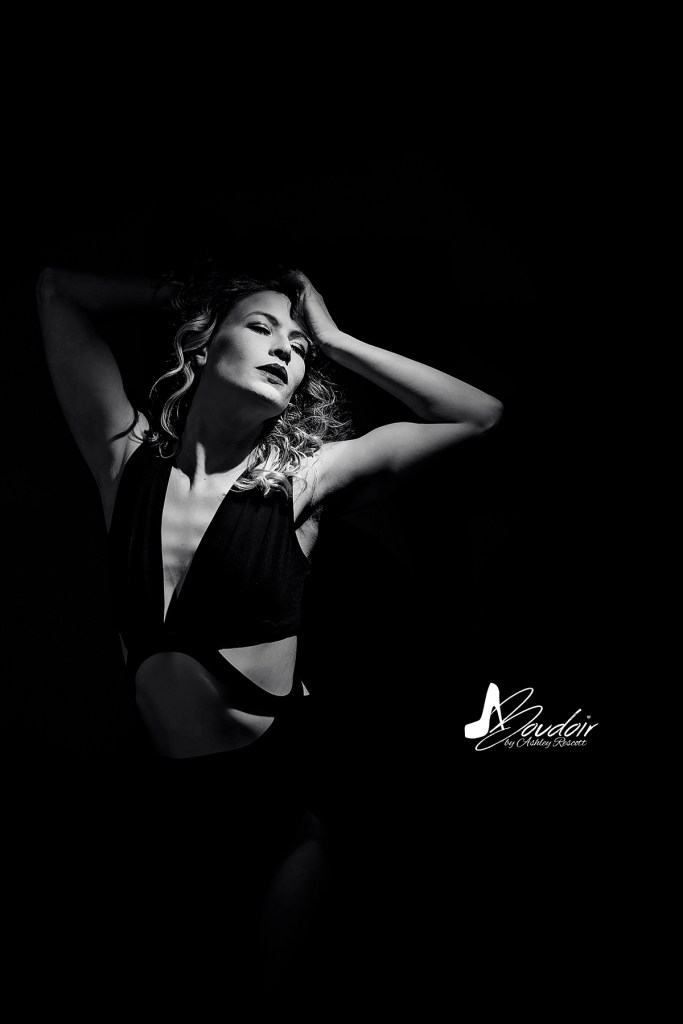 black and white boudoir portrait of woman spotlit with hands in her hair