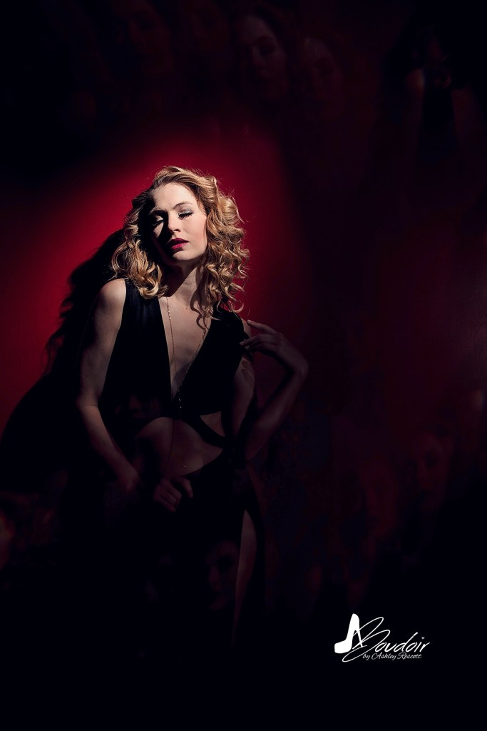 woman in black dress on red wall, spotlight