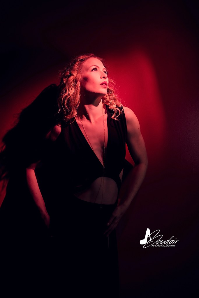 model in red spotlight during neon boudoir