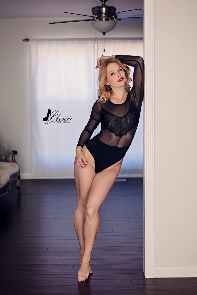 woman in body suit leaning against wall between rooms, natural light