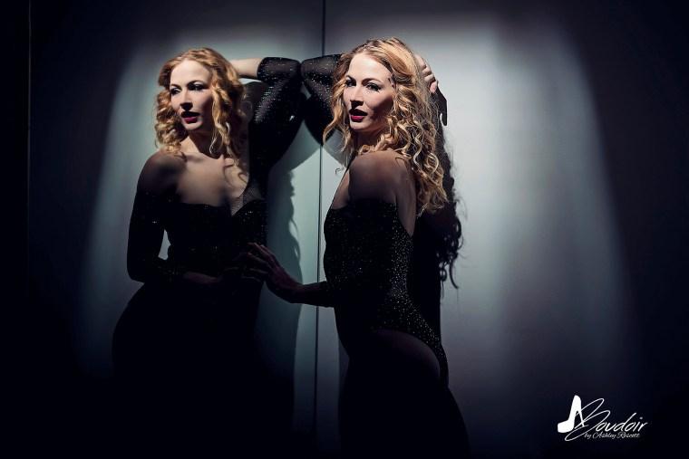 boudoir model in spotlight at mirror, looking over shoulder