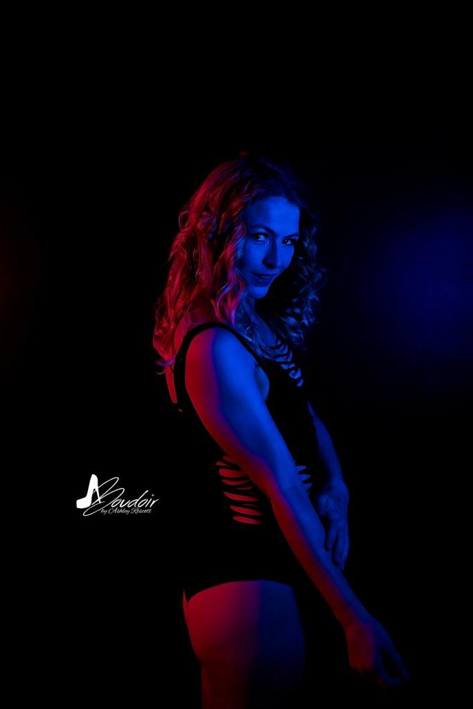 model in bodysuit in neon boudoir lighting