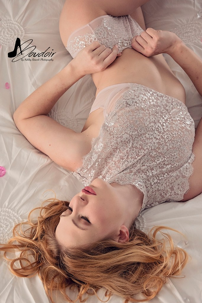woman in underwear lying in bed surrounded by gems