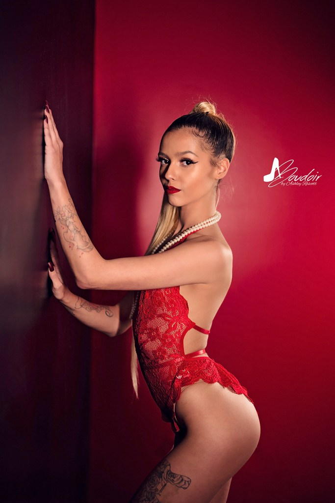 woman in red lace teddy standing near wall, dramatic boudoir