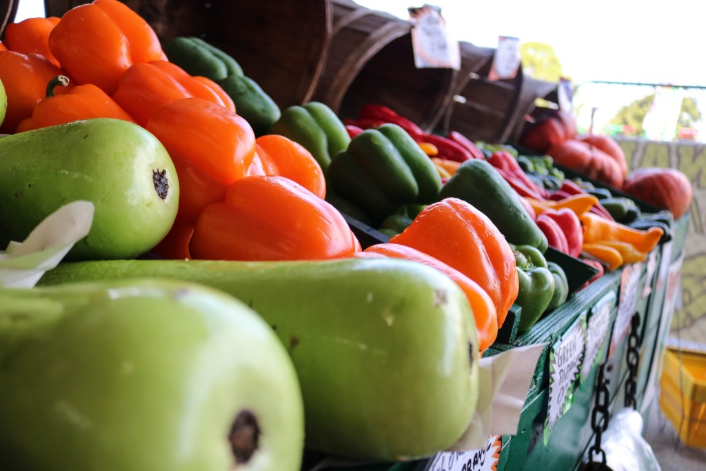 Green Peppers Orange Pepper Vegetables At Farmers Market With Kids