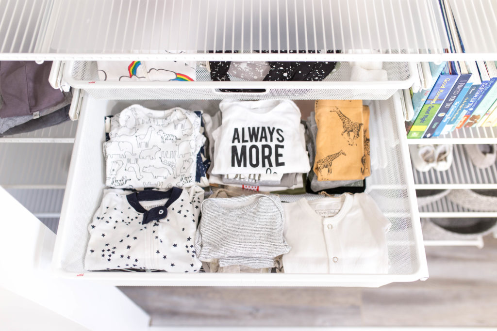 7 Baby Nursery Organization Ideas Every New Mom Should Follow by popular US life and style blogger Ashley Terk: image of a an organized closet by Organization and Relocation with a Custom Elfa Closet Design, pull out drawers from The Container Store containing folded baby shirts and pants.