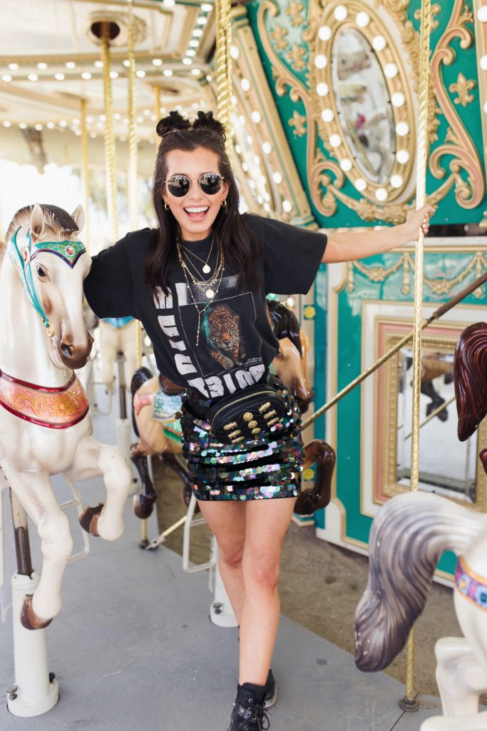 Revolve Festival Looks featured by top US fashion blogger Ashley Hodges; Image of a woman wearing black tee and sequin skirt.