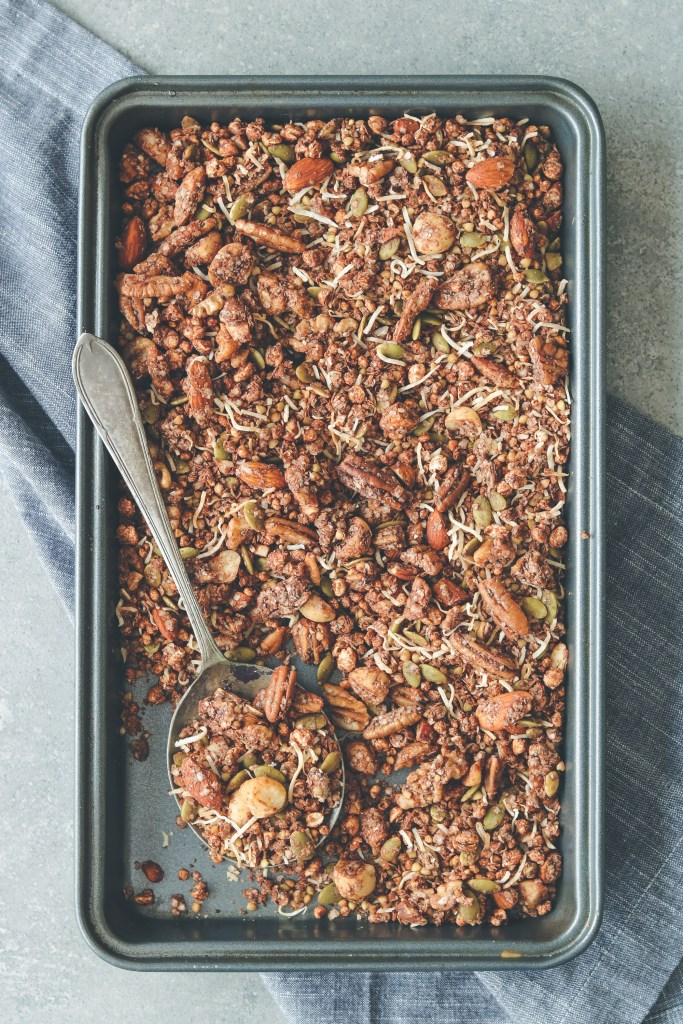 Overhead photo of choccie crunch granola on a baking tray, styled with a serving spoon and grey tea towel