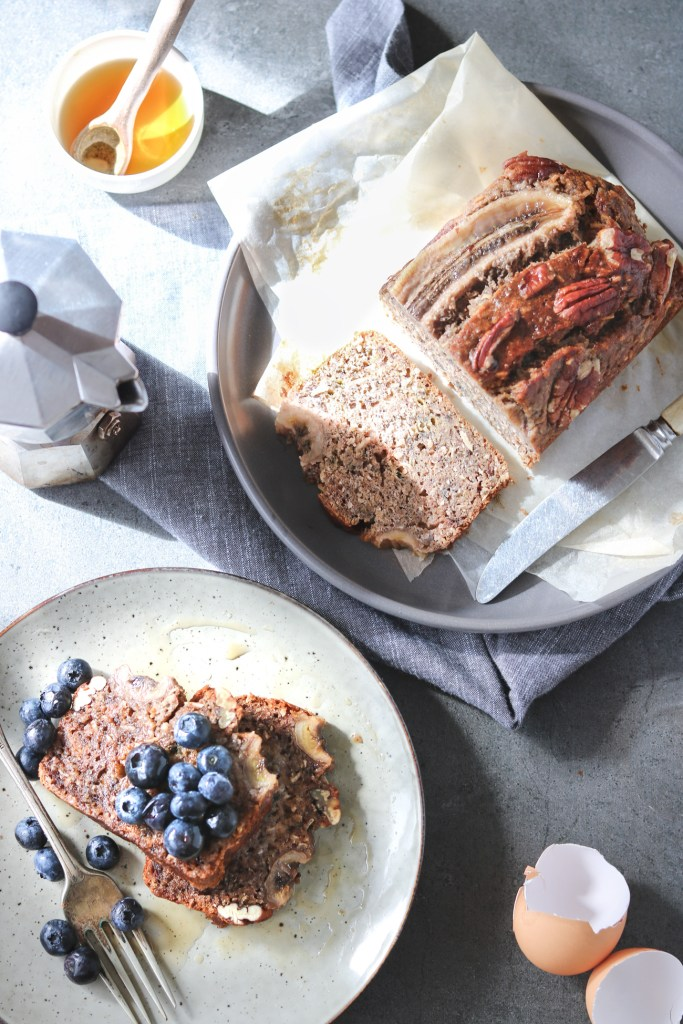 Overhead shot of two slices of banana bread served on a plate with fresh blueberries and maple syrup drizzled over, the rest of the loaf on another plate. Other elements seen in the frame are a small coffee perculator, egg shells and a small bowl of maple syrup