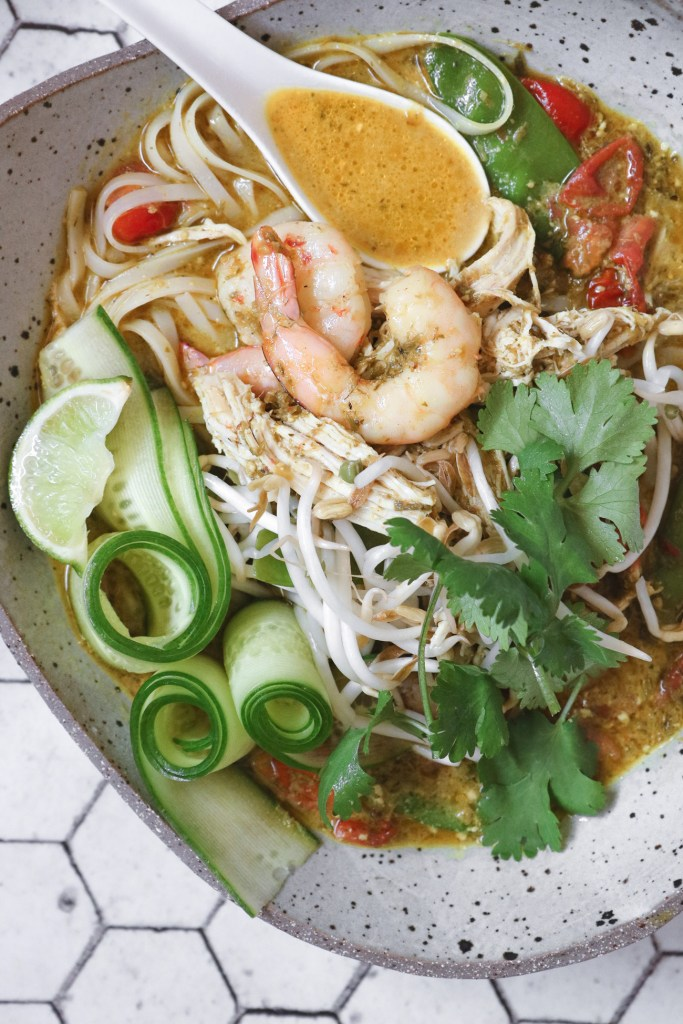 Close-up overhead shot of a bowl of fresh chicken and prawn curry laksa soup, garnished with coriander sprigs, bean sprouts, a lime wedge and rolled peeled cucumber