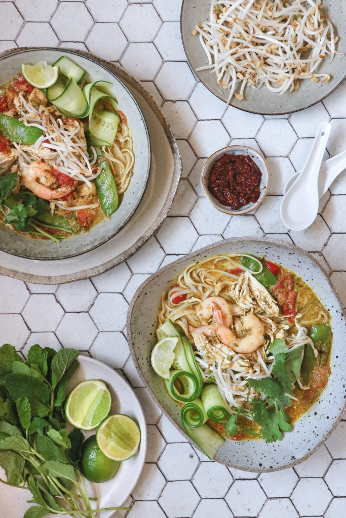Overhead shot of two bowls of low FODMAP chicken and prawn curry laksa soup, with side garnishes of bean sprouts, lime, chilli, coriander and mint on separate plates. Surface is white hexagonal tiles.