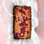 Overhead shot of raspberry, coconut and raspberry loaf in pan with baking paper overflowing on pink marble background