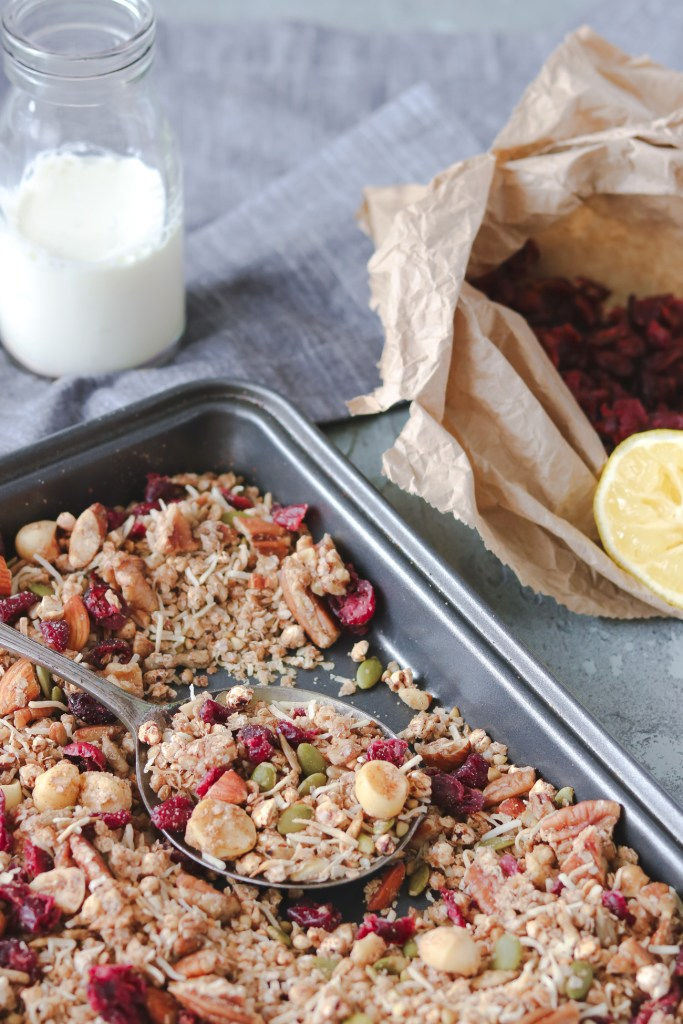 Front-on photo of a tray of lemon, ginger and cranberry granola. In the background, there is a glass bottle of milk, a brown paper bag with cranberries and half a lemon