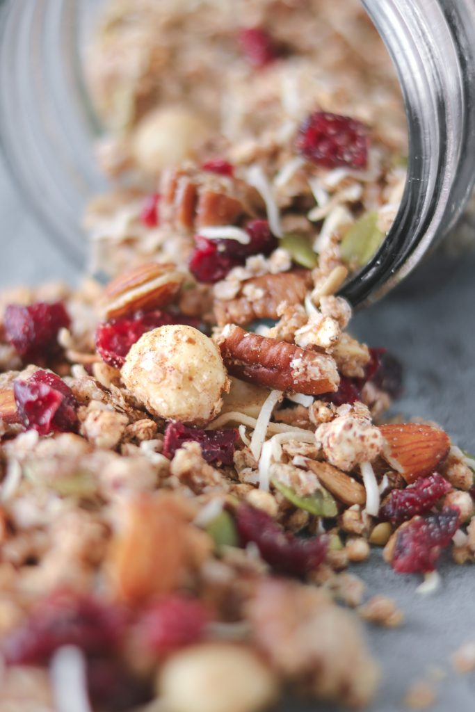 super close-up photo of a jar of lemon, ginger and cranberry granola that has been tipped over and is spilling out onto the table
