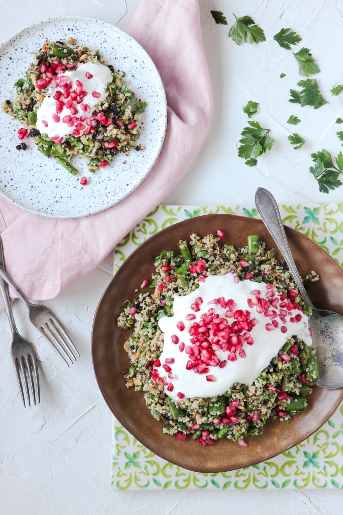 Overhead shot of Cypriot grain salad in a rust coloured serving bowl, topped with greek yoghurt and pomegranate seeds. Styled with a lime and aqua ceramic tile and soft pink napkin, and a smaller portion of the salad on a speckled plate off to the side