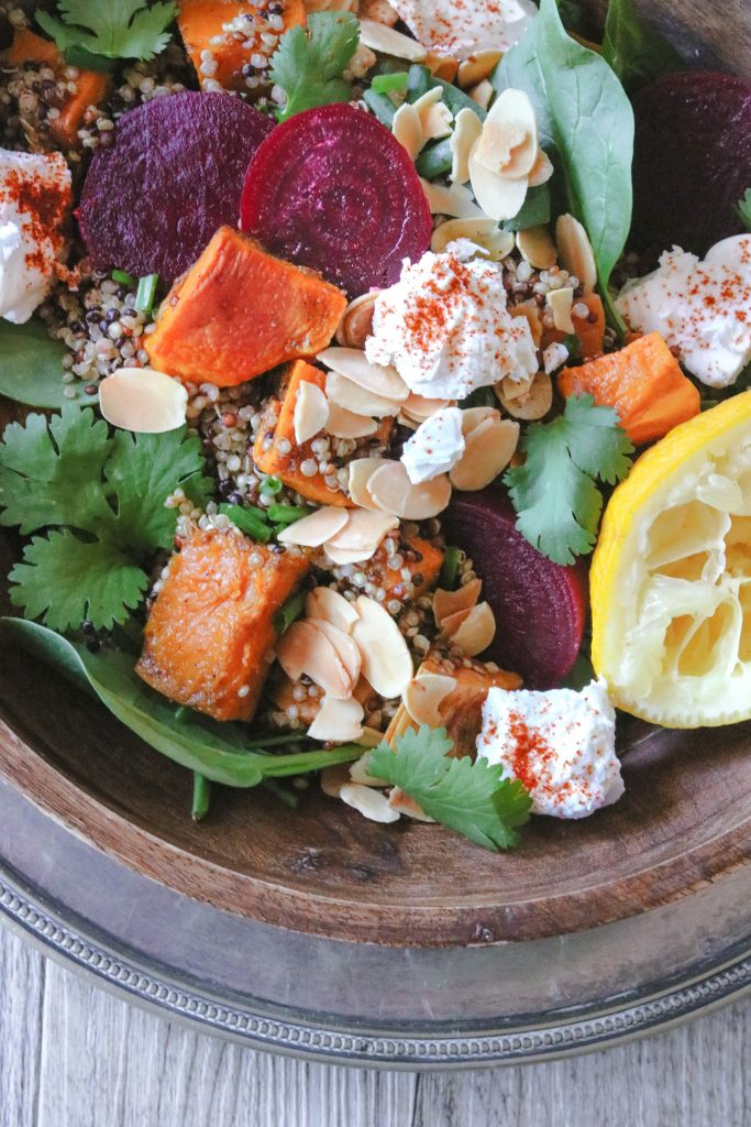 Overhead close-up photo of a wooden bowl filled with roasted pumpkin and sweet potato roasted salad with quinoa, lemon, herbs, roasted almonds, and paprika-sprinkled feta.