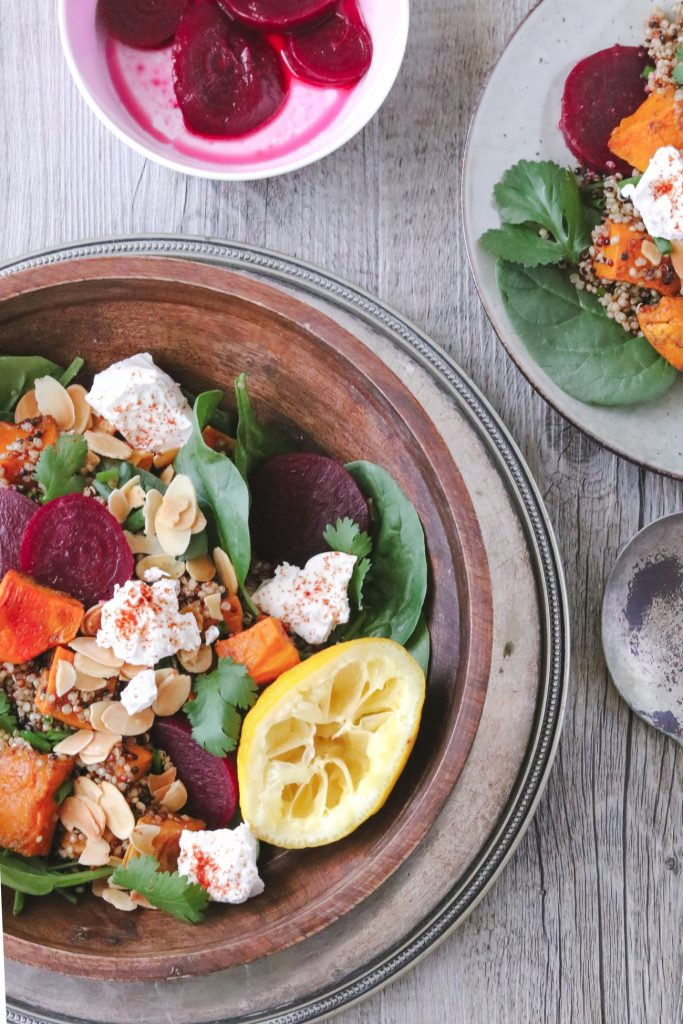 Overhead photo of a wooden bowl filled with roasted pumpkin and sweet potato roasted salad with quinoa, lemon, herbs, roasted almonds, and paprika-sprinkled feta. Another plate of salad and a small bowl of pickled beetroot slices can also be seen in the frame.