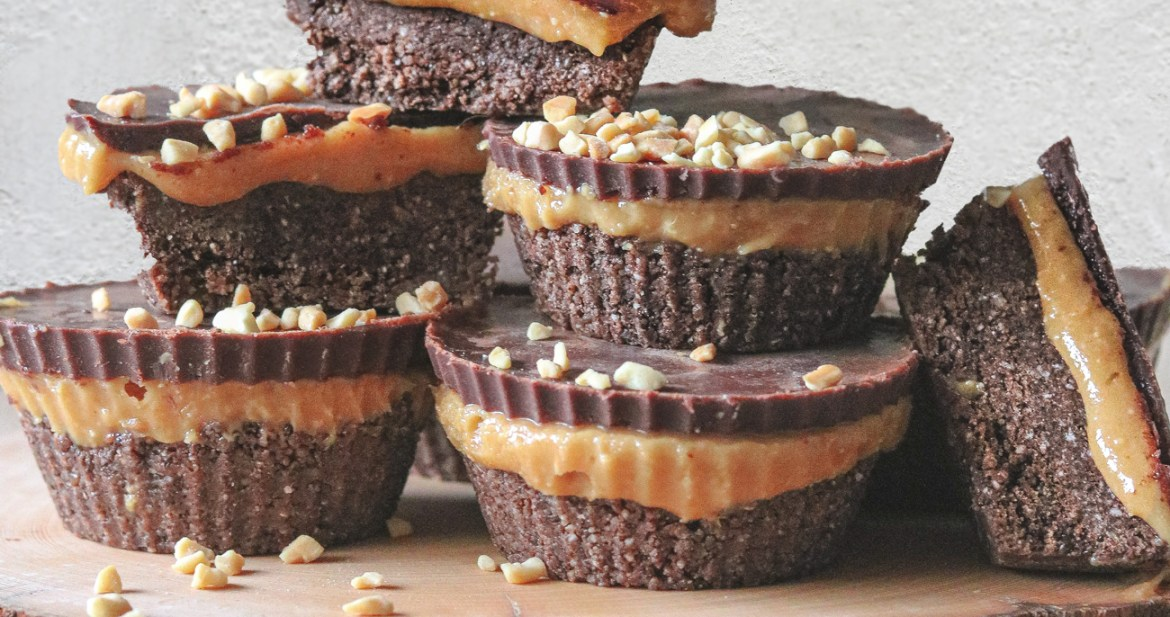 Front-on photo of peanut butter fudge cups stacked upon on a decorative wooden slice