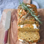 Photo of pumpkin, feta and chive loaf sitting on a wooden chopping board with an antique knife
