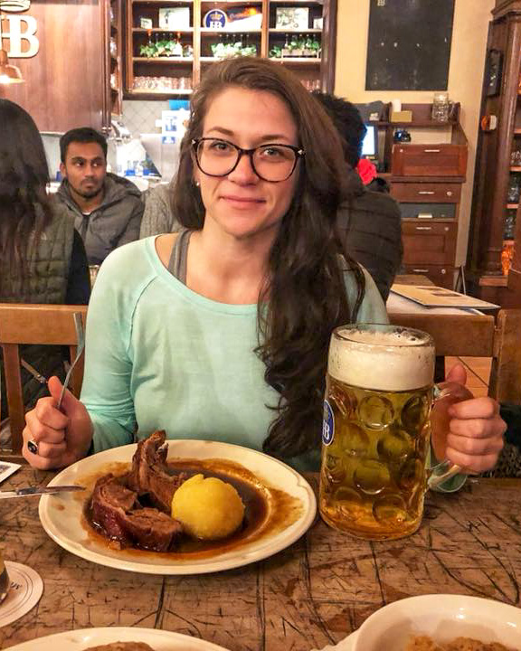 girl drinking a large beer at the Hofbräuhaus house in Munich on her road trip around Southern Germany