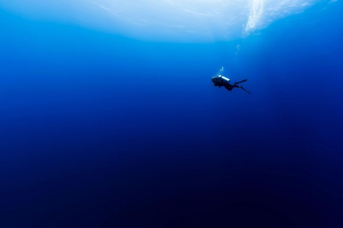 scuba diver in dark blue ocean from scuba diving life lessons post by ashmonster.com