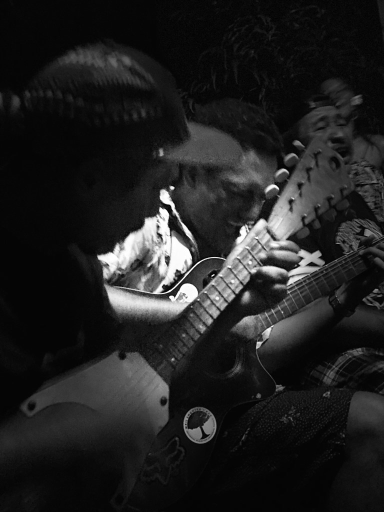 Black and white photo of boy playing the guitar