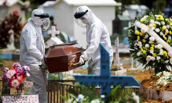 Gravediggers wearing protective suits carry the coffin of 68-year-old Natalina Cardoso Bandeira, who died after contracting coronavirus. Photograph: Bruno Kelly/Reuters