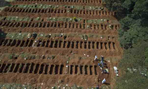 Workers in protective gear bury a person alongside rows of freshly dug graves at the Vila Formosa cemetery in Sao Paulo, Brazil. Photograph: André Penner/AP