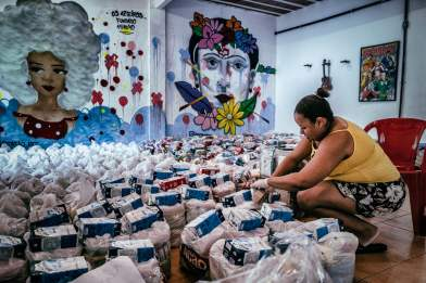 Volunteers prepare 'cestas basicas' (bags of basic necessities such as rice, beans and sugar) to distribute for the vulnerable and elderly in the City of God favela. Photograph: Nicoló Lanfranchi/The Guardian